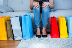 Woman sitting on couch with shopping bags Royalty Free Stock Photos