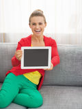 Woman sitting on couch and showing tablet pc Royalty Free Stock Image