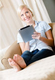 Woman sitting on the couch with silver pad Stock Image