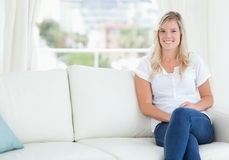 A woman sitting on the couch smiling Royalty Free Stock Photos