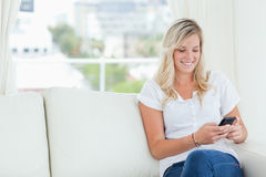 A woman sitting on the couch smiling as she uses her phone Royalty Free Stock Images