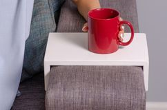 Woman sitting on the couch stand of cup in the hands of a cup stock photos
