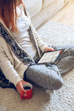 Woman sitting on the couch with tablet and coffee in hand Royalty Free Stock Images
