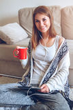 Woman sitting on the couch with tablet and coffee in hand Stock Photos