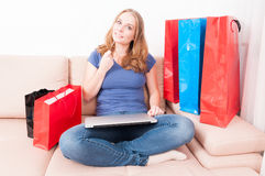 Woman sitting on couch thinking of making an online order. Holding laptop and credit or debit card Royalty Free Stock Images