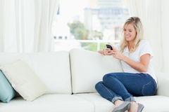 A woman sitting on the couch to the side as she uses her phone Royalty Free Stock Photo