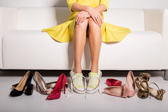 Woman sitting on couch and trying on shoes royalty free stock photo