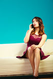 Woman sitting on couch using mobile phone. Royalty Free Stock Images