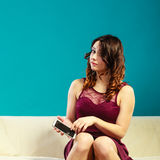 Woman sitting on couch using mobile phone. Royalty Free Stock Photography