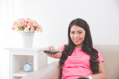 Woman sitting on a couch, using remote control Stock Images