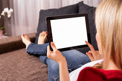 Woman sitting on couch and using tablet Stock Images