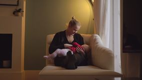 Happy mother breastfeeding eight months baby daughter
