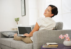 Woman sitting on couch and working on laptop Stock Image