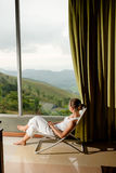 Woman is sitting in cozy armchair at hotel high up in mountains Royalty Free Stock Image