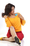 Woman sitting with credit card. Beautiful Woman sitting with credit card holding in her teeth Royalty Free Stock Image