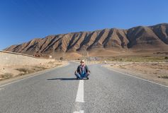 Woman sitting with cross leg on the road. Fork in the road. Morocco Stock Photography