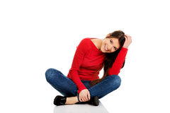 Woman sitting cross legged on the floor. Royalty Free Stock Photography