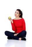Woman sitting cross-legged holding an apple Stock Image