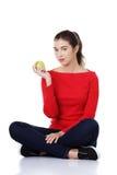 Woman sitting cross-legged holding an apple Stock Photo
