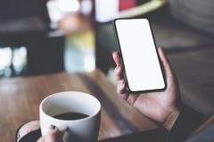 A woman sitting cross legged , holding black mobile phone with blank white desktop screen on thigh while drinking coffee. Mockup image of a woman sitting cross Royalty Free Stock Image