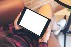 A woman sitting cross legged and holding black tablet pc with blank white screen on thigh in modern cafe. Mockup image of a woman sitting cross legged and Stock Photography