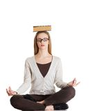 Woman sitting cross-legged holding book on head Royalty Free Stock Image