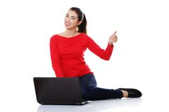 Woman sitting cross-legged with laptop pointing up Stock Photo