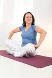 Woman sitting cross-legged on mat Stock Images