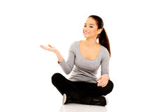 Woman sitting cross legged with open hand. Royalty Free Stock Image