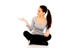 Woman sitting cross legged with open hand. Royalty Free Stock Photography