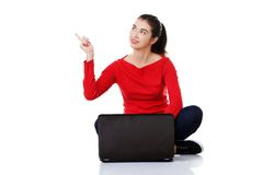 Woman sitting cross-legged pointing up Royalty Free Stock Photography