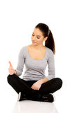 Woman sitting cross legged with thumbs up. Stock Images
