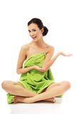 Woman sitting cross-legged wrapped in towel Royalty Free Stock Photos