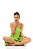 Woman sitting cross-legged wrapped in towel Stock Photo