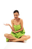 Woman sitting cross-legged wrapped in towel Stock Image