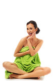 Woman sitting cross-legged wrapped in towel Royalty Free Stock Image