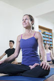 Woman sitting cross-legged in a yoga class Stock Photo