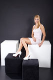 Woman sitting on cube Royalty Free Stock Photos