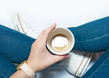Woman sitting with cup of coffee in hands stock photo