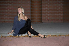 Woman sitting on a curb Stock Image