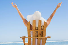 Woman sitting in deck chair at the beach with arms up Royalty Free Stock Photos