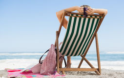 Woman sitting in deck chair at the beach with her beach bag and towel Stock Photos