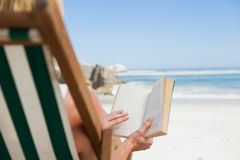 Woman sitting in deck chair at the beach reading Stock Photography