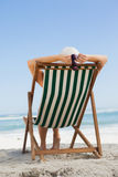 Woman sitting in deck chair at the beach Stock Photo