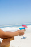 Woman sitting in deck chair with a cocktail at the beach Stock Images
