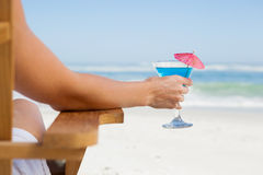 Woman sitting in deck chair with a cocktail at the beach Royalty Free Stock Image
