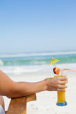 Woman sitting in deck chair with a cocktail at the beach Stock Image