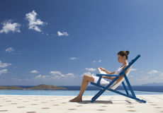 A woman sitting on a deck chair reading a book Stock Photo
