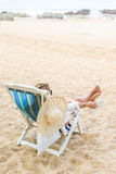 Woman sitting on a deck chair relaxing at the beach Royalty Free Stock Images