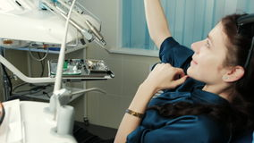 Woman sitting in a dental chair makes a photo with the medical staff. stock footage